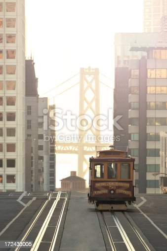 The Van Ness cable car as it reaches the top of Nob Hill in San Francisco on California Street with a view of the Bay Bridge in the background.