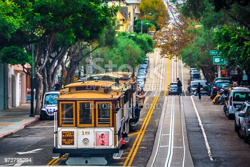 San Francisco, USA - November 4, 2017: Vintage cable car running up the steep street in San Francisco.  Invented in San Francisco near 150 years ago, cable cars have no engine or motor on themselves. They are pulled along by cables running beneath the street.