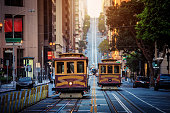 Classic view of historic traditional Cable Cars riding on famous California Street in beautiful early morning light at sunrise in summer with retro vintage style cross processing filter effect, San Francisco, California, USA