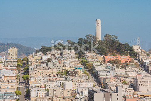 From the Russian Hill area of San Francisco, California, USA  the landmark Coit Tower can be seen surrounded by residential homes on Telegraph Hill. Photographed from a low angle view. Clear blue sky background.
