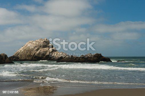 This is a color photograph of the Ocean Beach landscape in San Francisco, California during the summer. Rugged rocks stick out of the water along the shoreline of the Pacific ocean.