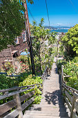 San Francisco, charming wooden staircase in Napier Lane, Telegraph Hill, with the Oakland Bay Bridge in background