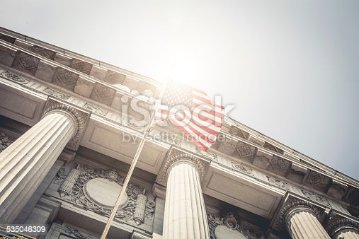 San Francisco City Hall entrance seen from below with a national flag.