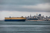 High quality stock photo of a blurry container ship passing through the San Francisco bay with the city in the background.