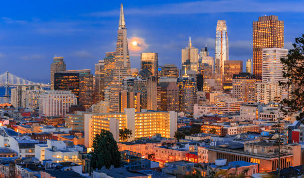 San Francisco downtown skyline at dusk with the full moon between the skyscrapers stock photo