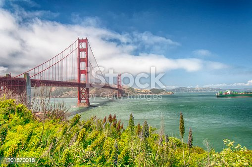 A cargo ship near the iconic Golden Gate bridge with the Marin Hills in the background against a blue sky in San Francisco California.
