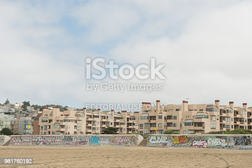 In San Francisco, USA in Ocean Beach residential buildings fill the land up to the sand, which has concrete barriers marked with graffiti.