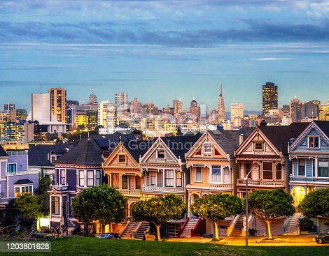 The famous row of Victorian style San Francisco townhouses, with the lights of downtown on the horizon in the distance.