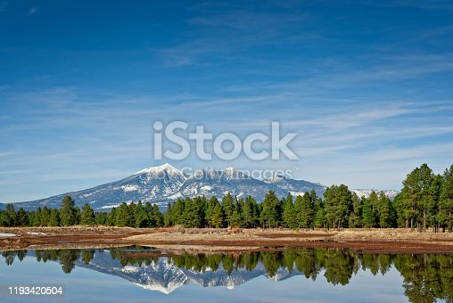 The San Francisco Peaks are the remnants of an ancient volcano that erupted millions of years ago, shattering a large mountain and leaving a large crater and surrounding peaks. The tallest of these are Humphreys at 12,637 feet and Agassiz at 12,356 feet. This picture of the snow-capped peaks reflected in a pond was taken from Kachina Wetlands in Kachina Village, Arizona, USA.