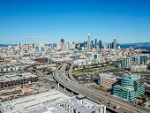 Aerial view of the San Francisco Skyline as the 280 Freeway empties into the city. Iconic skyscrapers fill the horizon. Mission Bay and the Bay Bridge are visible.