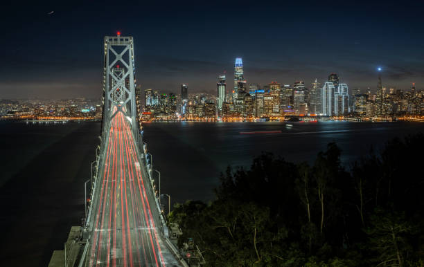 San Francisco skyline and Bay Bridge at night from Yerba Buena Island, California, USA a view of the San Francisco cityscape from above the San Francisco-Oakland Bay Bridge at dusk san francisco bay stock pictures, royalty-free photos & images
