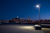 San Francisco skyline seen from parking lot with street light.