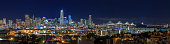 San Francisco city skyline panorama after sunset with city lights, the Bay Bridge and highway trail lights leading into the city in San Francisco, California, USA