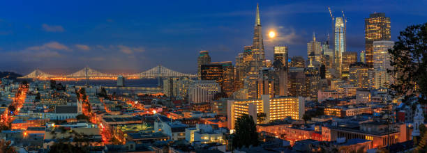 San Francisco skyline panorama at dusk with Bay Bridge and downtown skyline under a full moon stock photo
