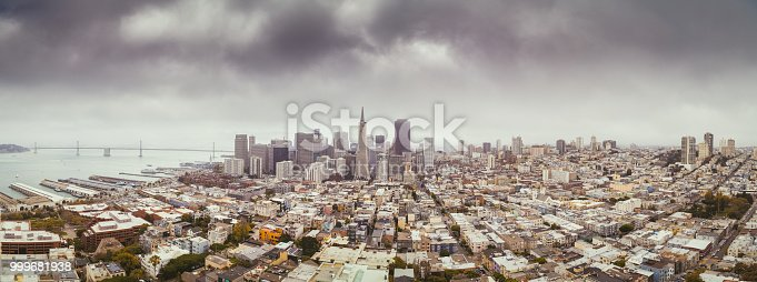 Classic aerial view of modern San Francisco skyline in summer with famous San Francisco fog rolling in seen from historic Coit Tower with retro vintage filter effect, San Francisco Bay Area, California, USA