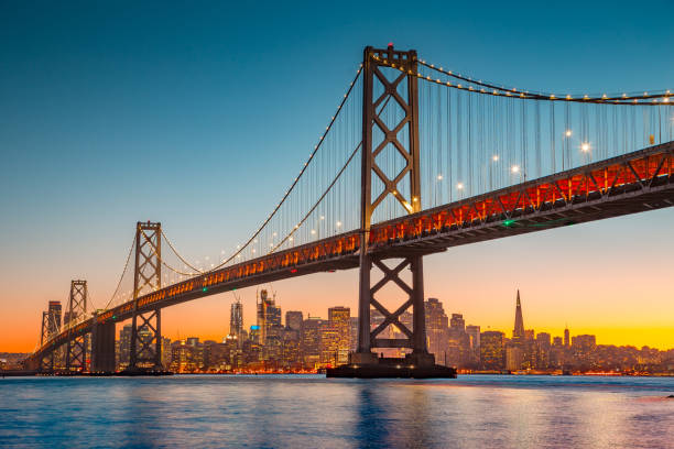 San Francisco skyline with Oakland Bay Bridge at sunset, California, USA Classic panoramic view of San Francisco skyline with famous Oakland Bay Bridge illuminated in beautiful golden evening light at sunset in summer, San Francisco Bay Area, California, USA golden gate bridge stock pictures, royalty-free photos & images