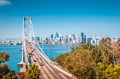 Classic panoramic view of San Francisco skyline with famous Oakland Bay Bridge illuminated on a beautiful sunny day with blue sky in summer, San Francisco Bay Area, California, USA
