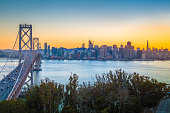 Classic panoramic view of famous Oakland Bay Bridge with the skyline of San Francisco illuminated in beautiful twilight with sunset glow in summer, California, USA