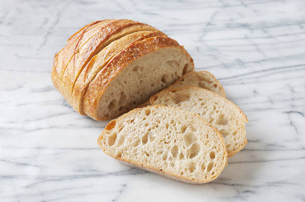 San Francisco Sourdough Bread A sliced loaf of San Francisco sourdough bread. round loaf stock pictures, royalty-free photos & images