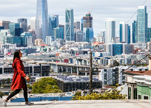 San Francisco, California, USA - May 17, 2018: Woman crossing the street in Potrero Hill. This district known for its views of the San Francisco Bay and city skyline.