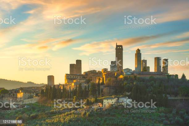 Photo of San Gimignano town skyline and medieval towers at sunset. Tuscany, Italy