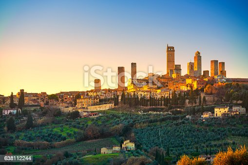 San Gimignano town skyline and medieval towers sunset. Italian olive trees in foreground. Tuscany, Italy, Europe.