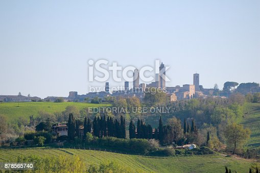 San Gimignano town skyline and medieval towers. Italian olive trees in foreground. Tuscany, Italy, Europe.