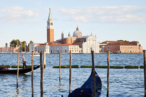 San Giorgio Maggiore island and basilica with gondola passing in Venice at sunset, Italy