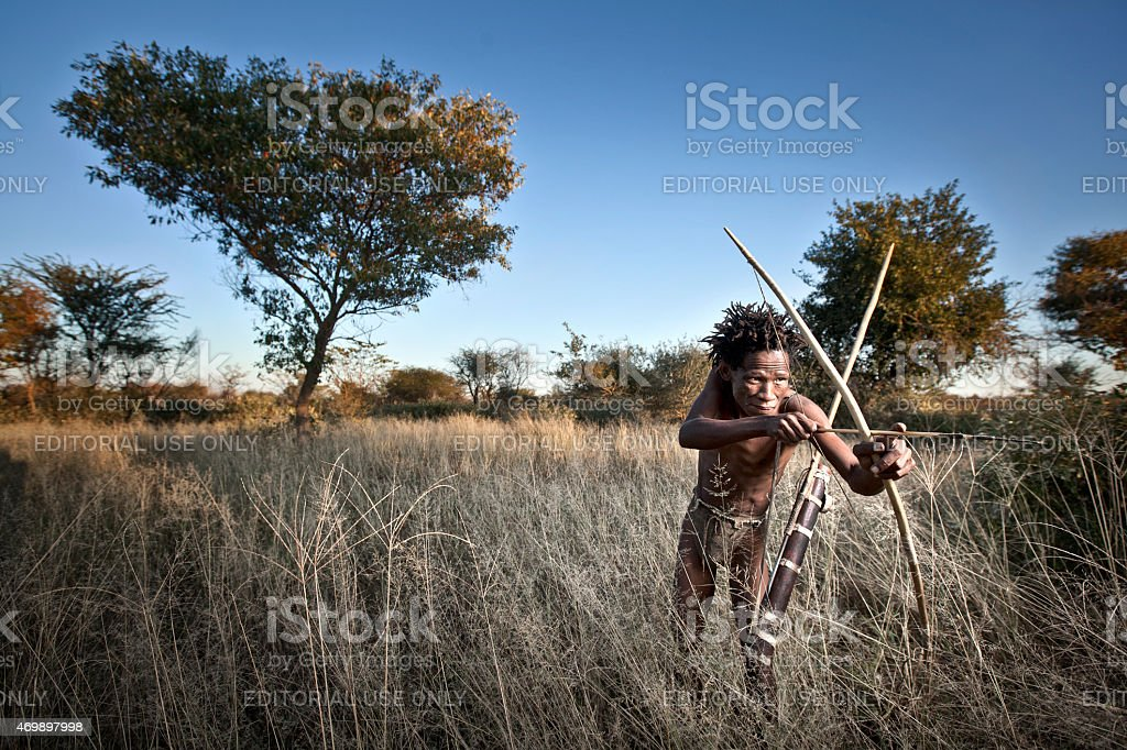 San hunter aims at a small antelope. stock photo