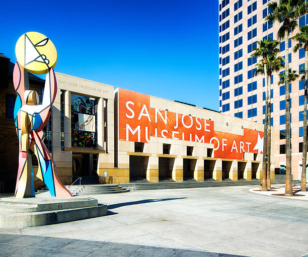 San Jose Califonia Museum of art side view with statue San Jose, USA - March 3, 2015: San Jose Califonia Museum of art side view with statue and giant red banner. Palm trees and Knight Ridder building visible in the frame. esplanade theater stock pictures, royalty-free photos & images
