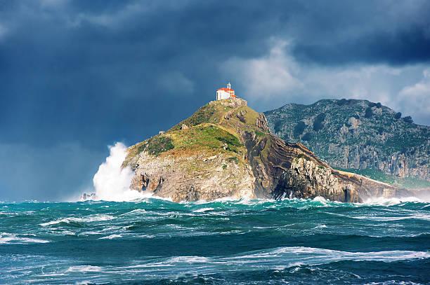 san juan de gaztelugatxe with rough sea stock photo