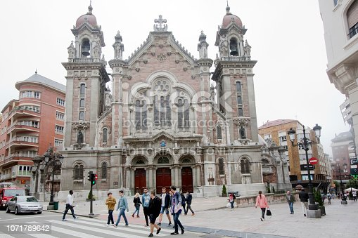 Oviedo, Spain-june 15, 2018: Horizontal view of San Juan el Real church, Oviedo, Asturias, Spain. Town square and young people passing by.
