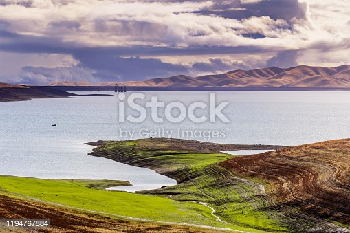 San Luis Reservoir on a stormy day; green grass starting to grow on the shoreline; San Luis Reservoir is a man-made lake storing water for agricultural purposes Merced County, Central California;