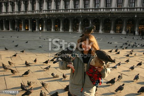 Girl with pigeons in San Marco Square in Venice