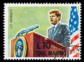 'A 1964 San Marino postage stamp with an illustration of President John Fitzgerald Kennedy standing behind a podium, with a USA flag in the background.  DSLR with macro lens; no sharpening.'