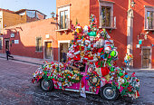 San Miguel de Allende, Guanajuato, Mexico - Nov 25, 2019: Man driving a Volkswagen, covered in christmas toys, driving around town, giving candy to children