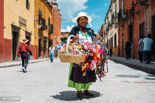 San Miguel de Allende, Guanajuato, Mexico - August 2017: Senior Mexican woman sells hand made traditional Mexican dolls on the streets of San Miguel de Allende.