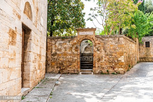 San Quirico D'Orcia, Italy Street alley empty nobody on road in small historic medieval town village in Tuscany during summer day stone architecture with garden courtyard entrance