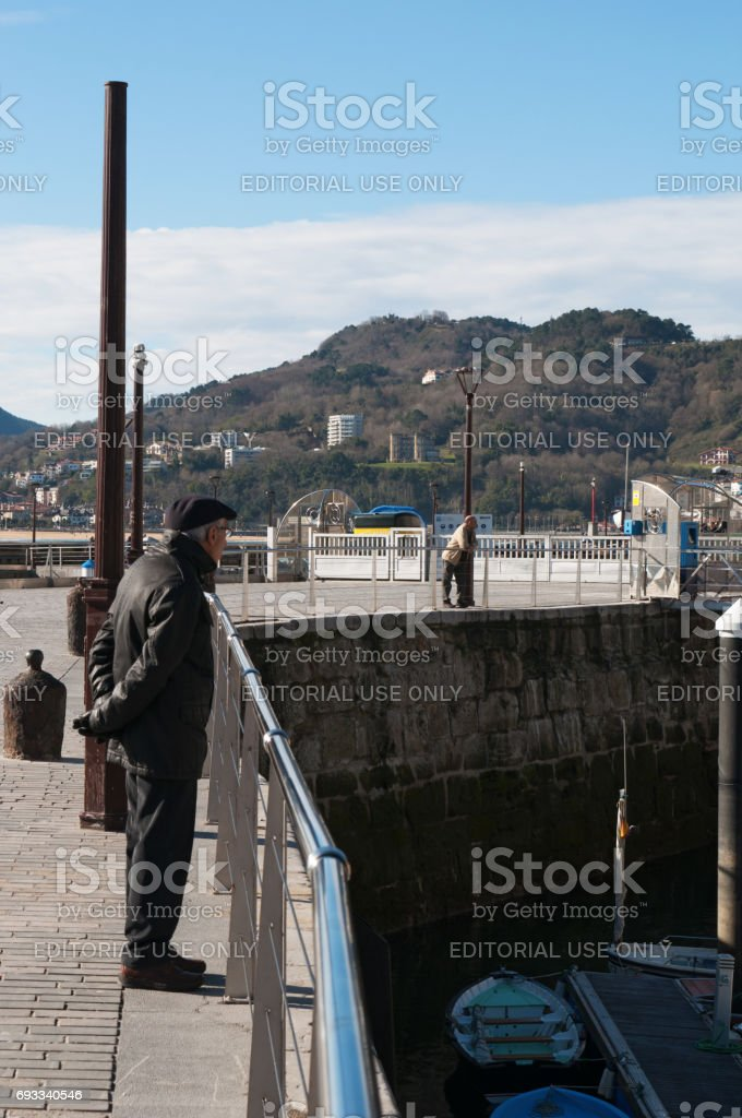 San Sebastian: an old man with a beret looking at the boats in the port and the skyline of Donostia San Sebastian, the coastal city on the Bay of Biscay stock photo