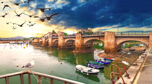 San Vicente de la Barquera.Cantabria. Idyllic and stunning coastal town in Spain. Bridge over the sea and sunset seascape. Boats in the harbor. cantabria stock pictures, royalty-free photos & images