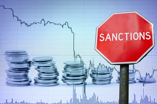 Sanctions sign against economy background with graph and coins.