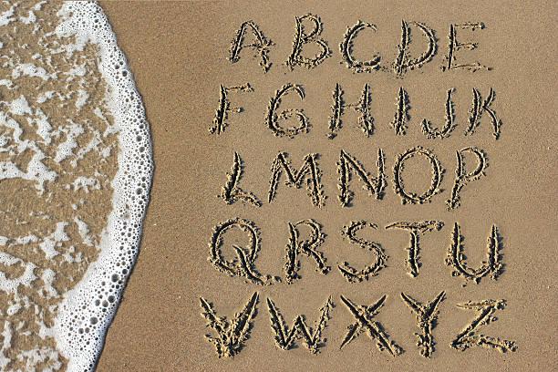 Sand Alphabet and Sea stock photo