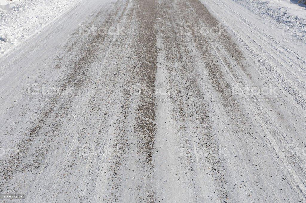 Sand and salt on snowy straight asphalt road stock photo