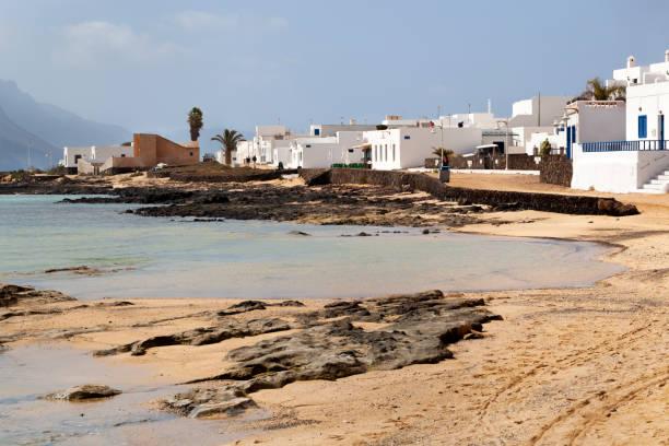 Zand-en witte huizen aan de kust van Caleta de Sebo foto