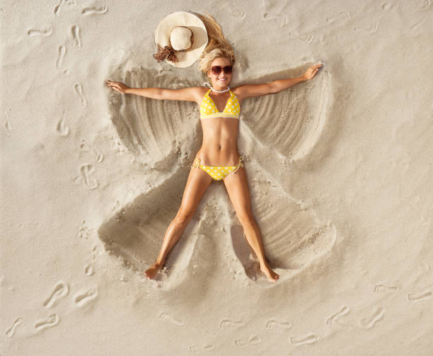 sand angel in polka dot bikini - reclining stock photos and pictures
