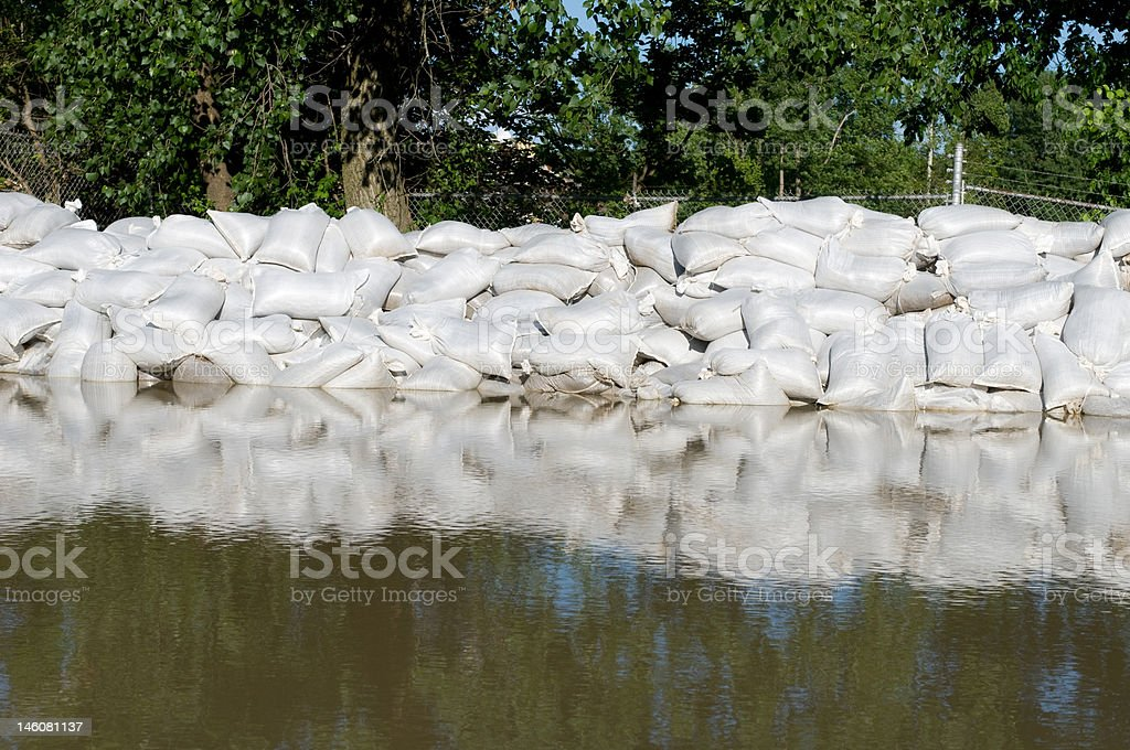 Sand bags and flood water stock photo