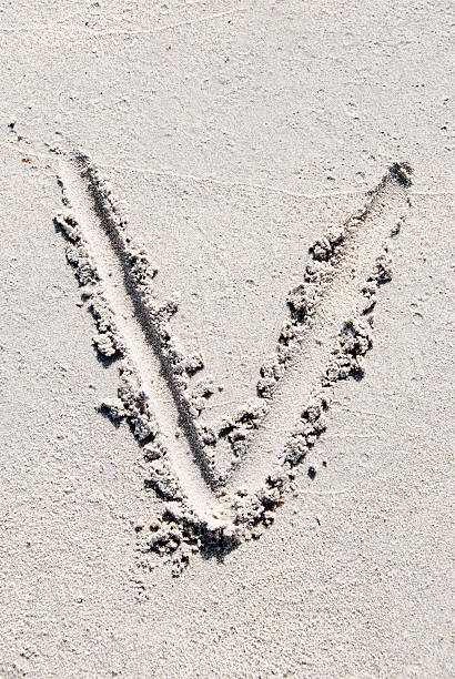 Sand beach alphabet: letter V stock photo