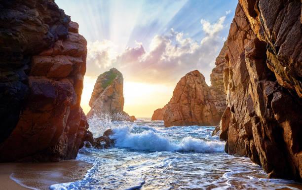 sand beach among rocks on evening sunset - riva dell'acqua foto e immagini stock