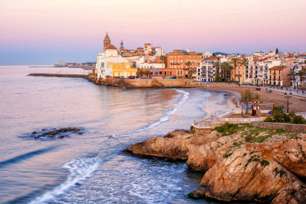 Sand beach and historical Old Town in mediterranean resort Sitges, Spain Sand beach and historical Old Town in mediterranean resort Sitges near Barcelona, Costa Dorada, Catalonia, Spain barcelona spain stock pictures, royalty-free photos & images