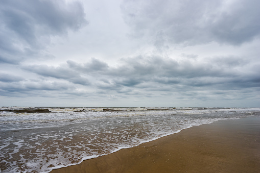 istock Sand beach, blue sea and white bubble wave in cloudy day 685846788